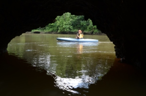 A natural limestone bridge frames Ramsey Cook as she paddles on the Flint River near Albany.