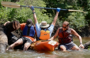 Taylor Morris and Chris Thompson lend a fellow paddler a lift over a cross-river strainer  during a grueling 17-mile paddle on day 2 of our journey.