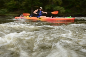 Cynthia Cox slides through shoals in downtown Albany during Day 1 of Fall Float on the Flint.